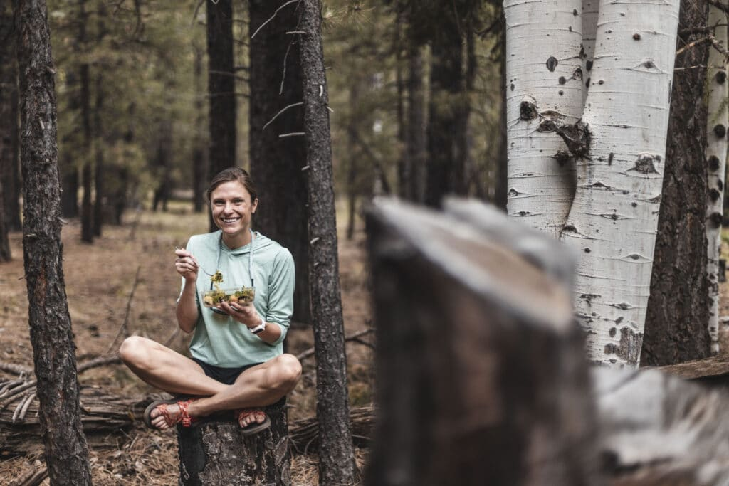 girl eating while sitting on top of a tree stump smiling at the camera